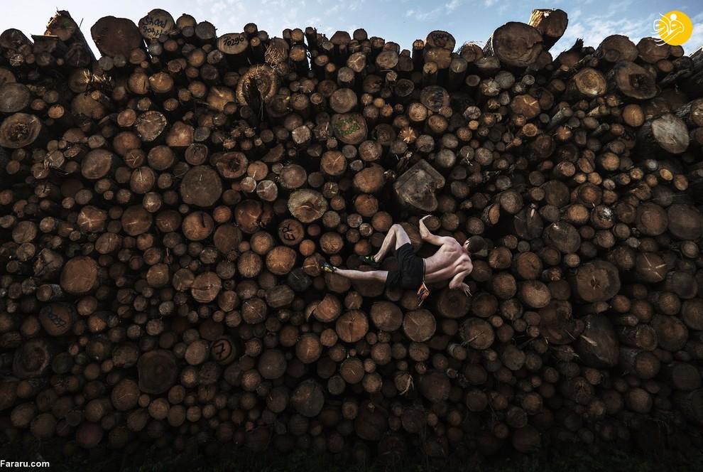 آدام پرتی، عکاس استرالیایی لحظهای را شکار کرده که یک صخرهنورد در ایالت بایرن آلمان به جای صخره و سنگ به تنههای درختان انبارشده آویزان است. این ورزشکار تقریبا به صورت افقی خود را نگاه داشته است. او بدون کمربند ایمنی و یا طناب در حال تمرین است. این عکس مقام اول را از به تصویر کشیدن ورزشهای فردی کسب کرد.